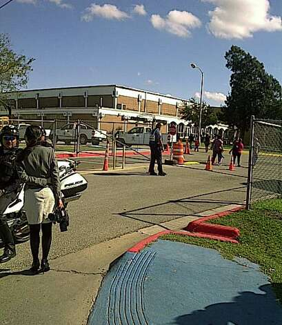 Brownsville students wait to be picked up after a shooting at a middle school where Brownsville police shot and killed a 15 year old after he pointed a gun at them. Photo: LYNN BREZOSKY, SAN ANTONIO EXPRESS-NEWS / SAN ANTONIO EXPRESS-NEWS