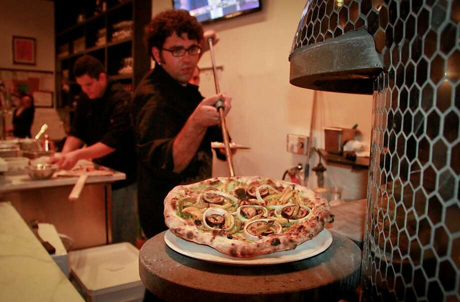 Jesse Ragsdale pulls a pizza from the oven at Mozzeria restaurant in San Francisco, Calif., on Thursday, December 29th,  2011. Photo: John Storey
