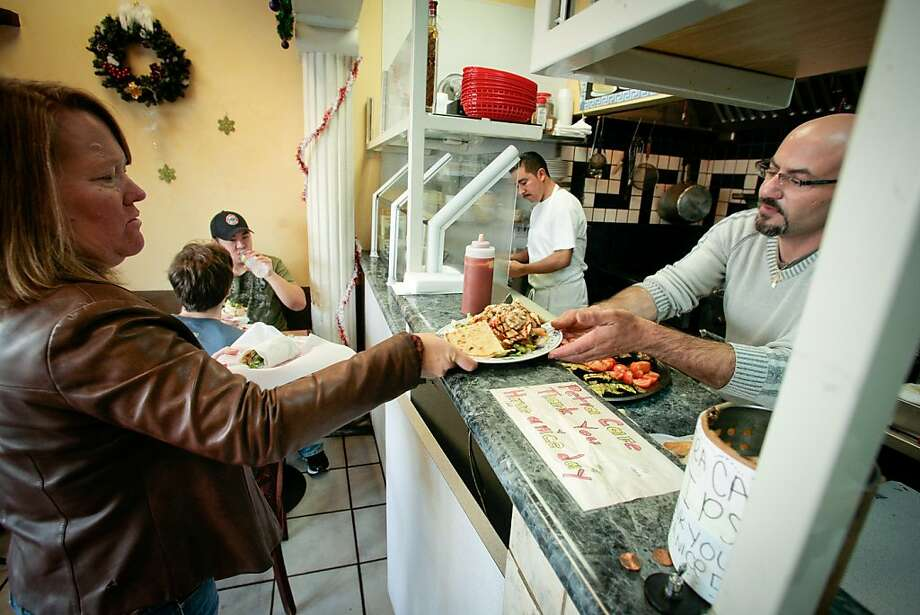 Owner of the Petra Cafe, Azmi Masarweh, hands food to a customer in Orinda, Calif., on Thursday, December 29th, 2011. Photo: John Storey, Special To The Chronicle