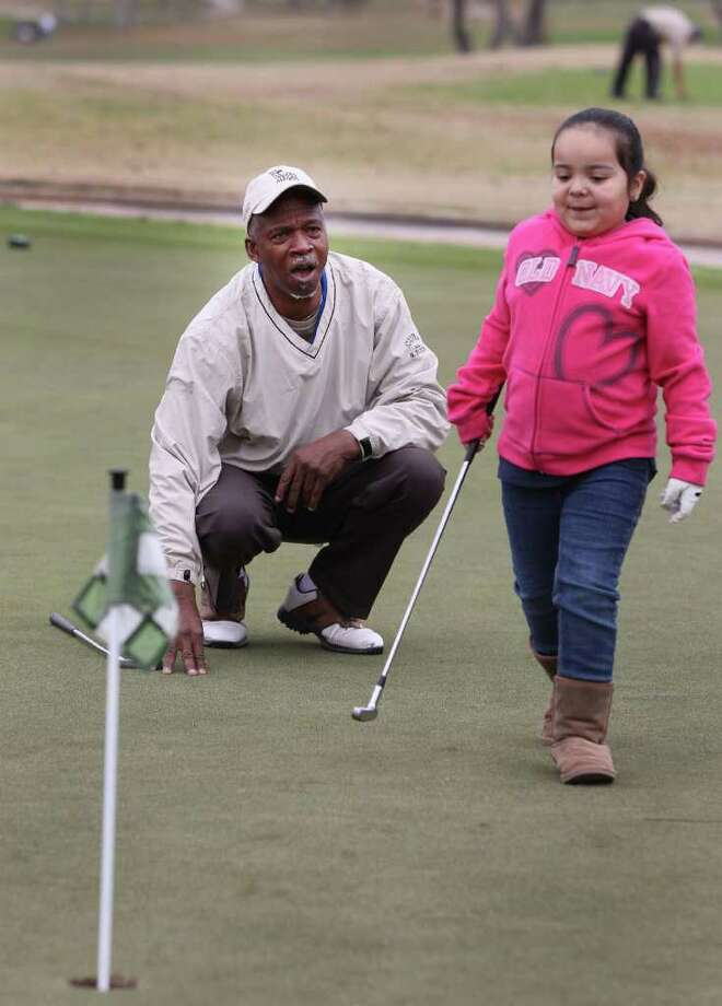 Larry Whitfield (left) offers encouragement to Jade Castro,6, after she made a putt Sunday December 18, 2011 at the Pecan Valley Golf Club. Whitfield, founder and president of the San Antonio Junior Golf Foundation, helps economically disadvantaged kids learn the game of golf and places an emphasis on education by ecouraging youth to get golf scholarships. Photo: SAN ANTONIO EXPRESS-NEWS