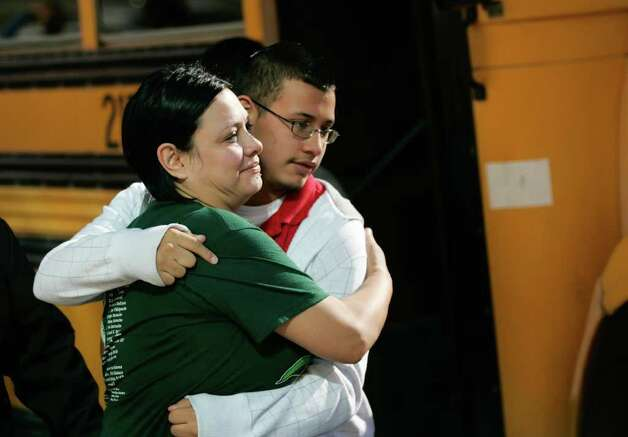 Jennifer Davila, left, tightly embraces her son Jordan as he is escorted into a park near Cummings Middle School, Wednesday, Jan. 4, 2012, in Brownsville Texas, after a fatal shooting at the school Wednesday morning. Officers summoned to a locked-down Texas middle school on Wednesday shot and killed an eighth-grader after he ignored their order to drop a handgun he was brandishing and instead pointed it at them, police said. Photo: The Brownsville Herald, Yvette Vela