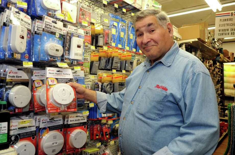 Store manager Larry Weiner, shows the display of smoke and carbon monoxide detectors at Feinsod Hardware Wednesday, Jan. 4, 2012. Photo: Helen Neafsey / Greenwich Time