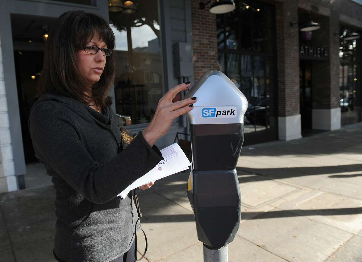 Susan Harms feeds a meter on Filmore St. on January 04, 2012. San Francisco is collecting less money from parking fines and more money from the meters under San Francisco's innovative parking management program. Parking is priced according to availability. Drivers use an iPhone app to find empty parking spaces.