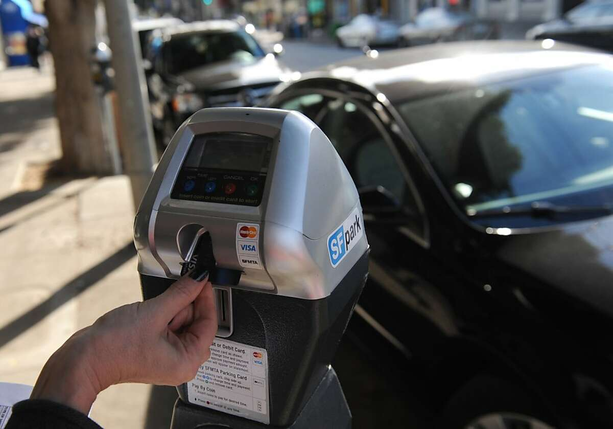 A meter is fed on Filmore St. on January 04, 2012. San Francisco is collecting less money from parking fines and more money from plugging the meters under San Francisco's innovative parking management program.