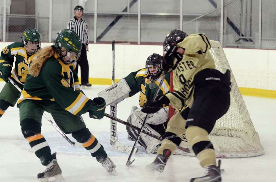 Greenwich Academy's goalie Annie DeFrino (1) guards the net as teammate Mary Taussig (8) fends off Westminster's Molly O'Sullivan (20) during the girls ice hockey game at Hamill Rink in Greenwich on Wednesday, Jan. 4, 2012. Photo: Amy Mortensen / Connecticut Post Freelance