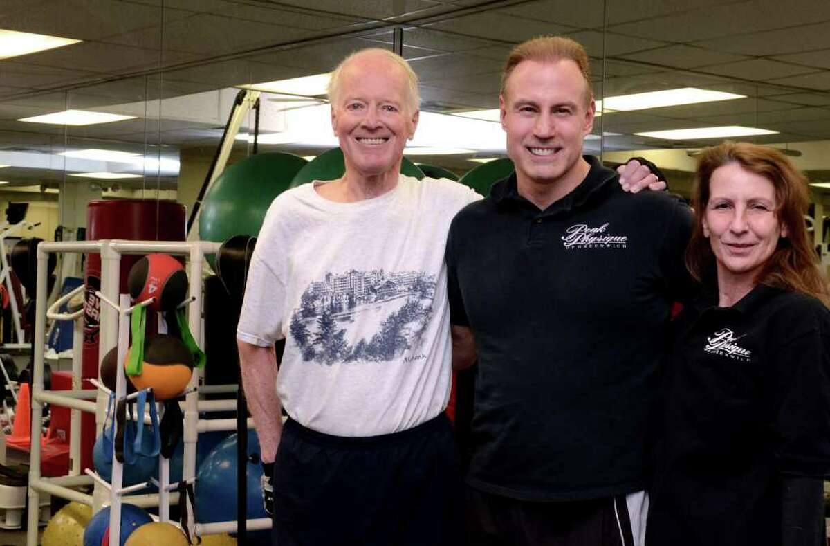 Dominic Novak, President of Peak Physique of Greenwich, center, stands with client Ed Bragg, at left, and trainer Sharon Stadtmiller in the Peak Physique studio located at 50 Holly Hill Lane in Greenwich on Monday, Dec. 19, 2011. Bragg is Novak's longest member, having joined in 1993. Stadtmiller has been a trainer at Peak Physique since 1994.