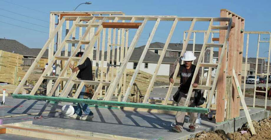 Two builders, both named Jose Hernandez, frame a house in the Vineyard Meadow subdivision in Katy.  An analyst says builders will start at least 20,000 single-family homes in the Houston area this year, about a 10 percent increase over 2011. Photo: Gary Fountain / Copyright 2012 Gary Fountain