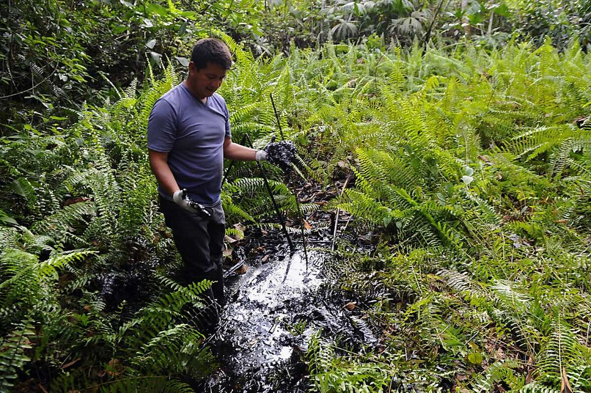 (FILE) File picture dated February 20, 2011 shows Ecuadorean activist of the Amazonia Defense Front, Donald Moncayo, showing waste of oil at Aguarico 4 oil well, near La Primavera, Sucumbios province, 45 km south of Lago Agrio, in the Ecuadorean Amazonia. A court in Ecuador on Tuesday fully upheld a 2011 ruling requiring US oil giant Chevron to pay $9.5 billion for environmental damage in the Amazon rainforest. AFP PHOTO / RODRIGO BUENDIA (Photo credit should read RODRIGO BUENDIA/AFP/Getty Images)
