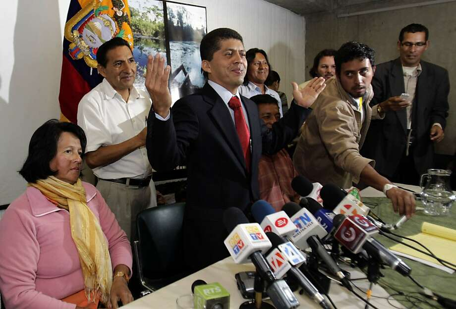 Pablo Fajardo, center, attorney for plaintiffs who won a court judgment against U.S. energy giant Chevron, gives a press conference in Quito, Ecuador, Wednesday Jan. 4, 2012.   An Ecuadorean court on Tuesday ratified a 2011 judgment penalizing Chevron for environmental damage allegedly caused since the 1960s.  Plaintiffs say they'll seek to collect as much as $18 billion through courts around the world, including by confiscating the company's assets and freezing its international accounts. At left is Carmen Zambrano, representative for non-indigenous residents affected by oil pollution.  (AP Photo/Dolores Ochoa) Photo: Dolores Ochoa, Associated Press