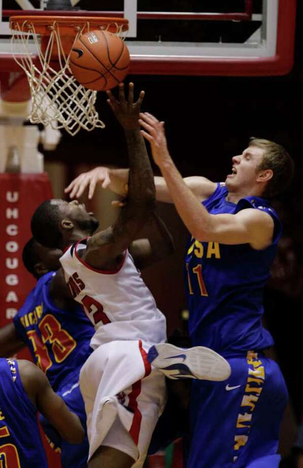 UH's Jonathon Simmons is fouled by Tulsa's Steven Idlet during overtime. Simmons then sank a free throw for the winning point over Tulsa. Photo: Melissa Phillip, Houston Chronicle / © 2011 Houston Chronicle