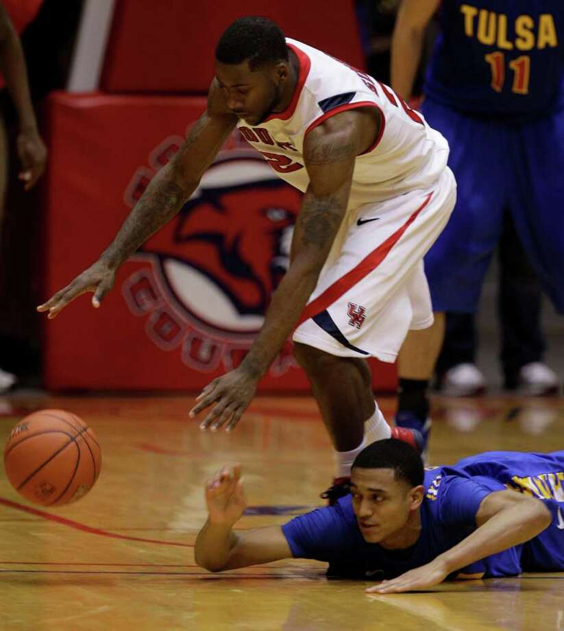 UH's Jonathon Simmons, left, regains control of the ball after a failed steal attempt by Tulsa's Jordan Clarkson during overtime. Photo: Melissa Phillip, Houston Chronicle / © 2011 Houston Chronicle