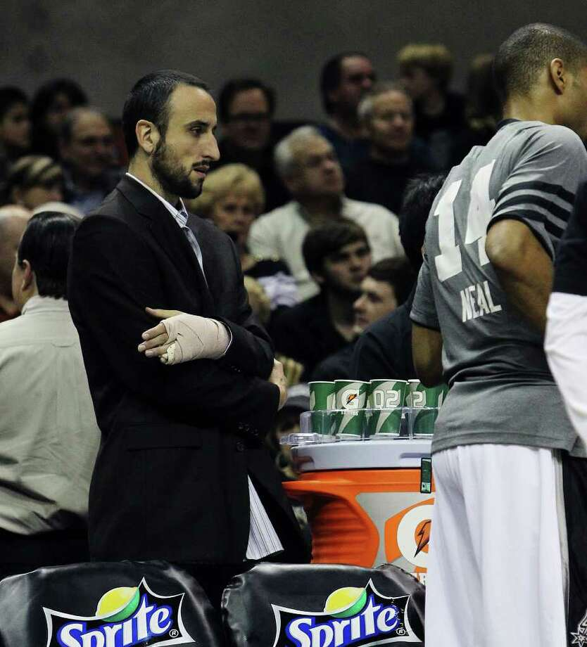 Spurs' Manu Ginobili (left) is seen with his bandaged left hand on the sidelines during a game against the Golden State Warriors in the first half at the AT&T Center on Wednesday, Jan. 4, 2012. Kin Man Hui/kmhui@express-news.net Photo: KIN MAN HUI, Express-News / SAN ANTONIO EXPRESS-NEWS
