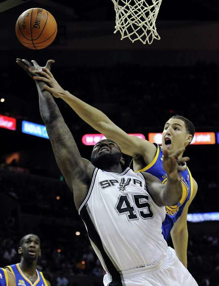 Spurs' DeJuan Blair (45) scores on a foul against the Golden State Warriors' Klay Thompson (11) in the first half at the AT&T Center on Wednesday, Jan. 4, 2012. Kin Man Hui/kmhui@express-news.net Photo: KIN MAN HUI, Express-News / SAN ANTONIO EXPRESS-NEWS