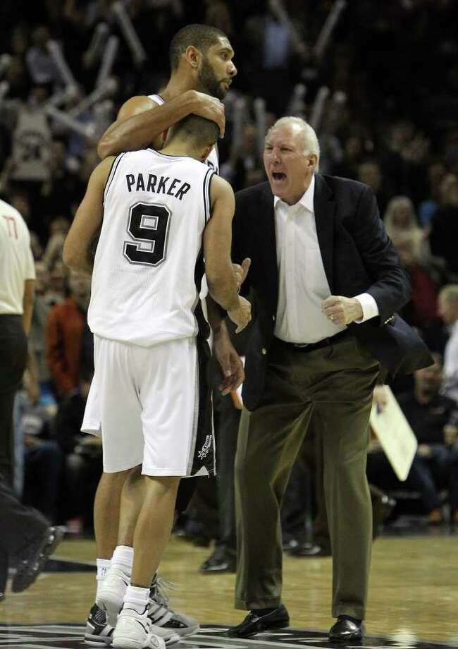 Spurs coach Gregg Popovich (right) reacts to his point guard Tony Parker (09) as teammate Tim Duncan congratulates Parker after scoring late in the fourth against the Golden State Warriors in the second half at the AT&T Center on Wednesday, Jan. 4, 2012. Spurs won 101-95. Kin Man Hui/kmhui@express-news.net Photo: KIN MAN HUI, Express-News / SAN ANTONIO EXPRESS-NEWS
