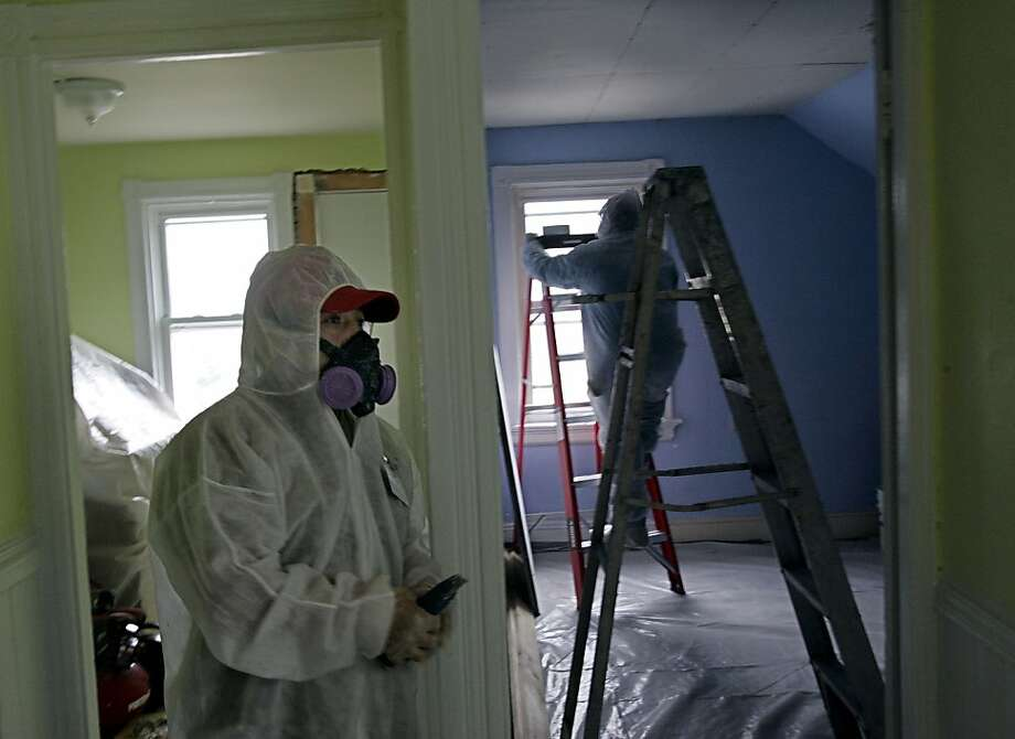 In this Thursday, Feb. 23, 2006 photo, contractors Luis Benitez, foreground, and Jose Diaz, background, clean up lead paint in a contaminated building in Providence, R.I. A federal panel recommended Wednesday, Jan. 4, 2012 that the threshold for lead poisoning in children should be lowered. If adopted by government officials, hundreds of thousands of additional U.S. children could be classified as having lead poisoning. Recent research persuaded panel members that children could suffer harm from concentrations of lead lower than the old standard, Centers for Disease Control and Prevention officials said. (AP Photo/Chitose Suzuki) Photo: Chitose Suzuki, Associated Press