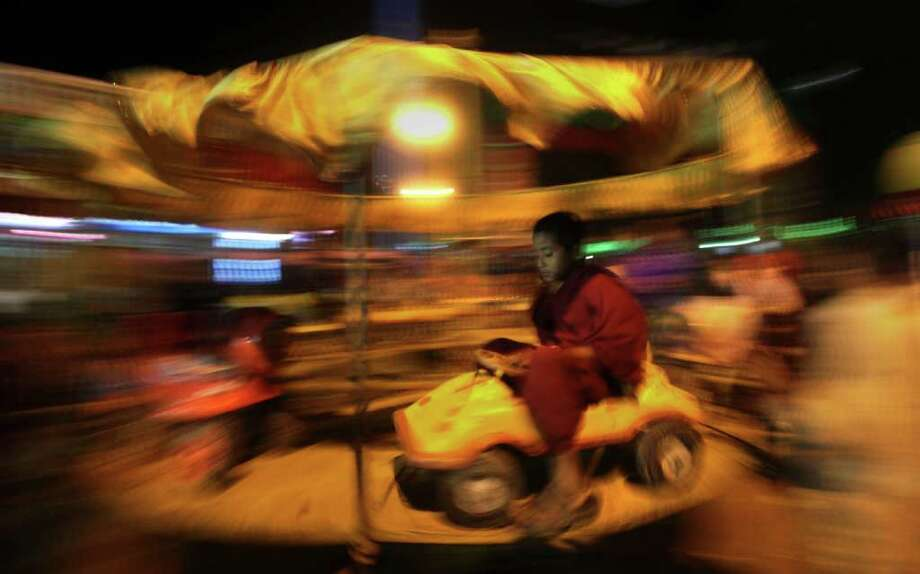 A young Buddhist monk takes a fairground ride near the venue of Kalachakra Buddhist festival in Bodh Gaya, Bihar state, India, Thursday, Jan. 5, 2012. Bodh Gaya is believed to be the place where Buddha attained enlightenment.(AP Photo/Altaf Qadri) Photo: Altaf Qadri, Associated Press / AP