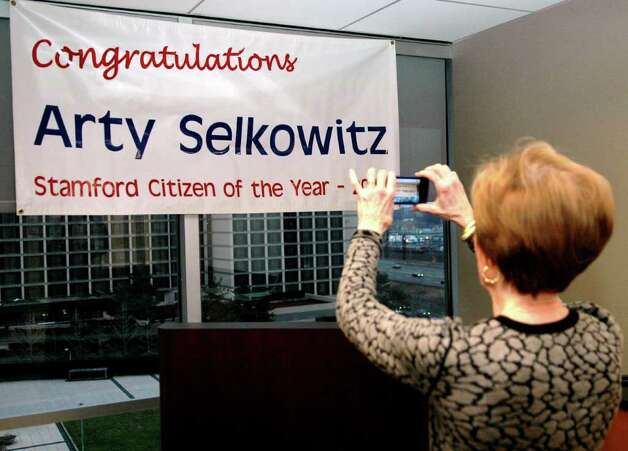 Betsey Selkowitz takes a photo of the sign that honors her husband, Arty as Stamford's Citizen of the Year for 2011. Family and friends gathered at Purdue Pharma in Stamford Conn. for the announcement on Thursday, Jan. 5, 2012. Photo: Cathy Zuraw / Stamford Advocate
