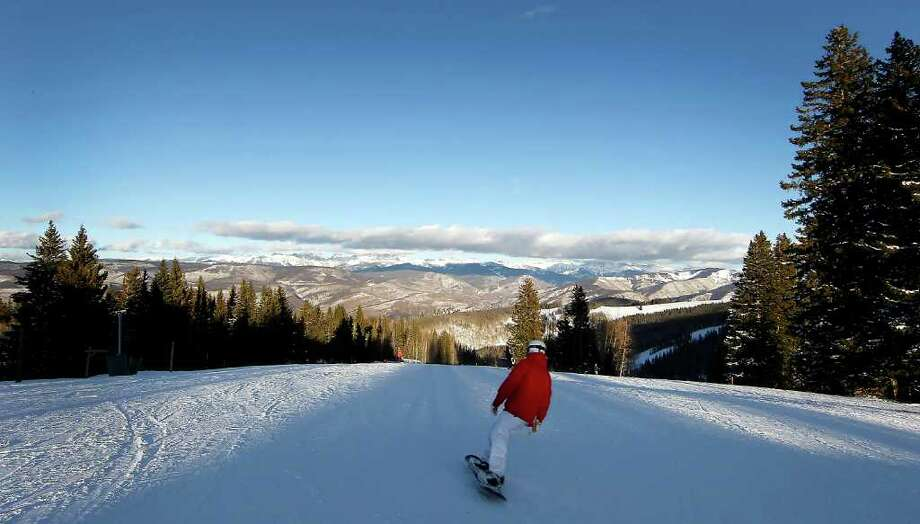 A snowboarder rides down a slope in Beaver Creek, Colo. Once guests get past the well-heeled lifestyle, they will find a world-class mountain, with all the peace, ruggedness and snowy beauty they could wish for. Photo: George Frey / © 2011 Bloomberg Finance LP