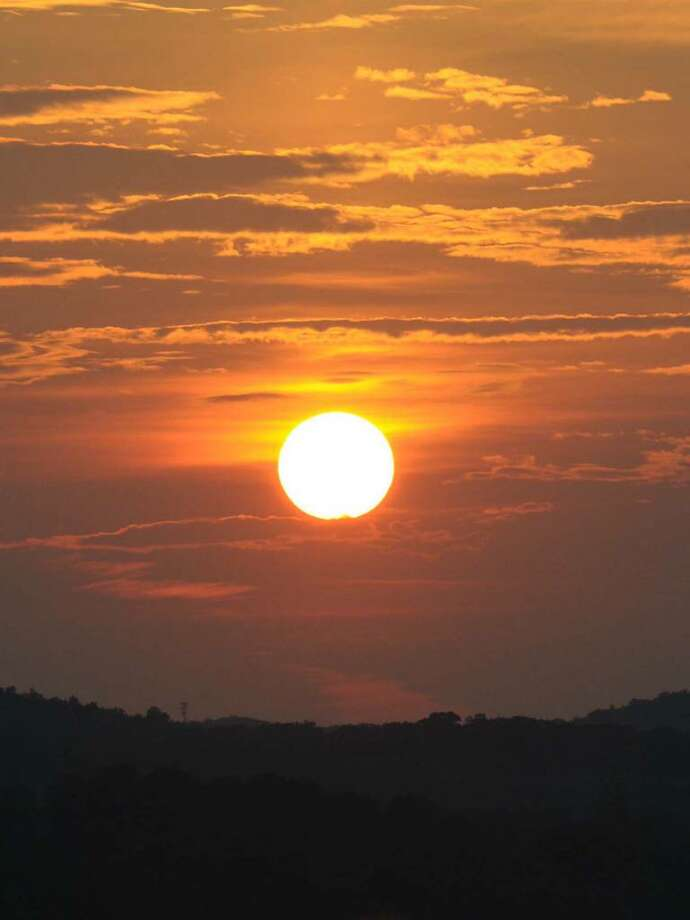 The sun sets over the mountains behind the Danbury Mall after a hazy, hot summer Wednesday, Aug. 19, 2009. Photo: Lisa Weir / The News-Times
