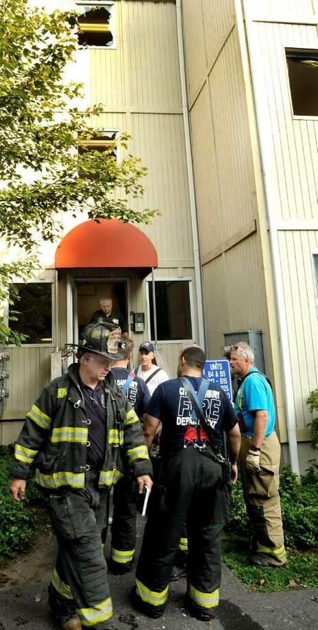 Danbury Fire Marshall John Osborne, front left, leaves the site of an early morning fire at Riverbend Conds on thursday, Aug.5. Photo: Michael Duffy / The News-Times