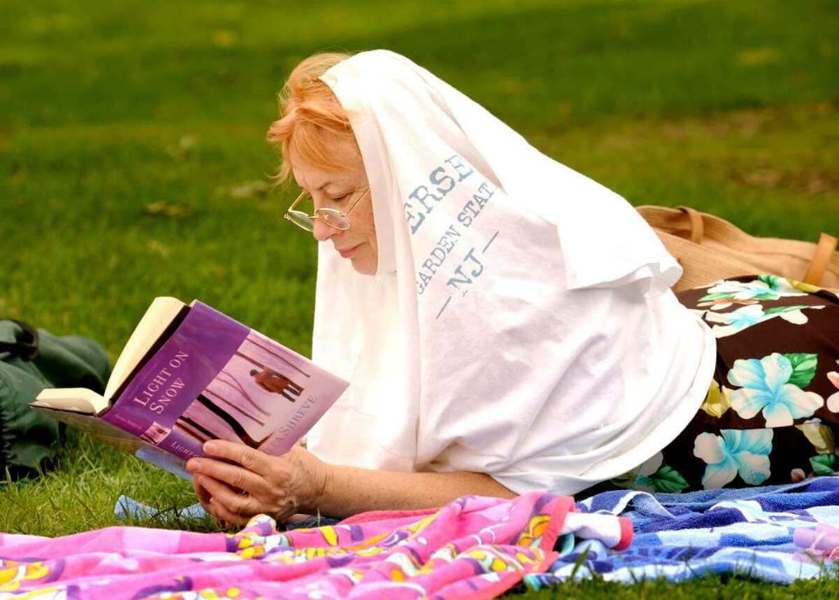 Jean MacKenzie, of Bethel, takes shelter from the sun, while relaxing at the beach, at Candlewood Shores in Brookfield on Aug.24,2009.