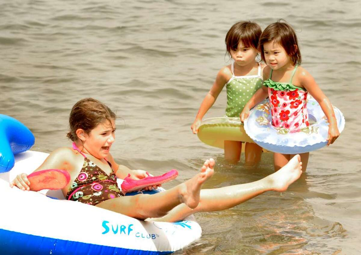 Isabela Scaglione, 9, of the Bronx, struggles to remain upright while twin sisters Vivian, left, and Olivia Aldrich, 4, of Brookfield watch, at the beach in Candlewood Shores in Brookfield on Aug.24,2009.