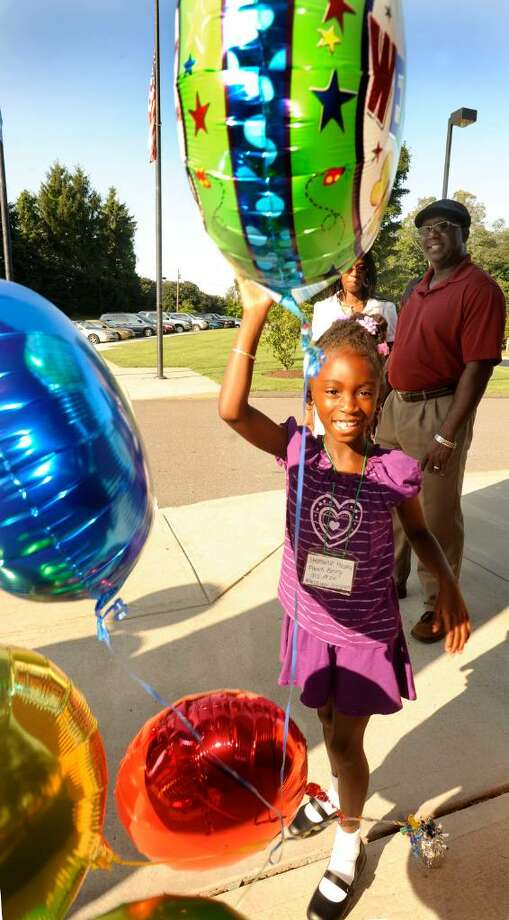 Kathy and Stephen Mosley watch as their daughter Stephanie, 6, bats welcome balloons out of her way at the enterance to the Frank A. Berry school in Bethel on her first day of first grade., Aug.25.2009. Photo: Michael Duffy / The News-Times