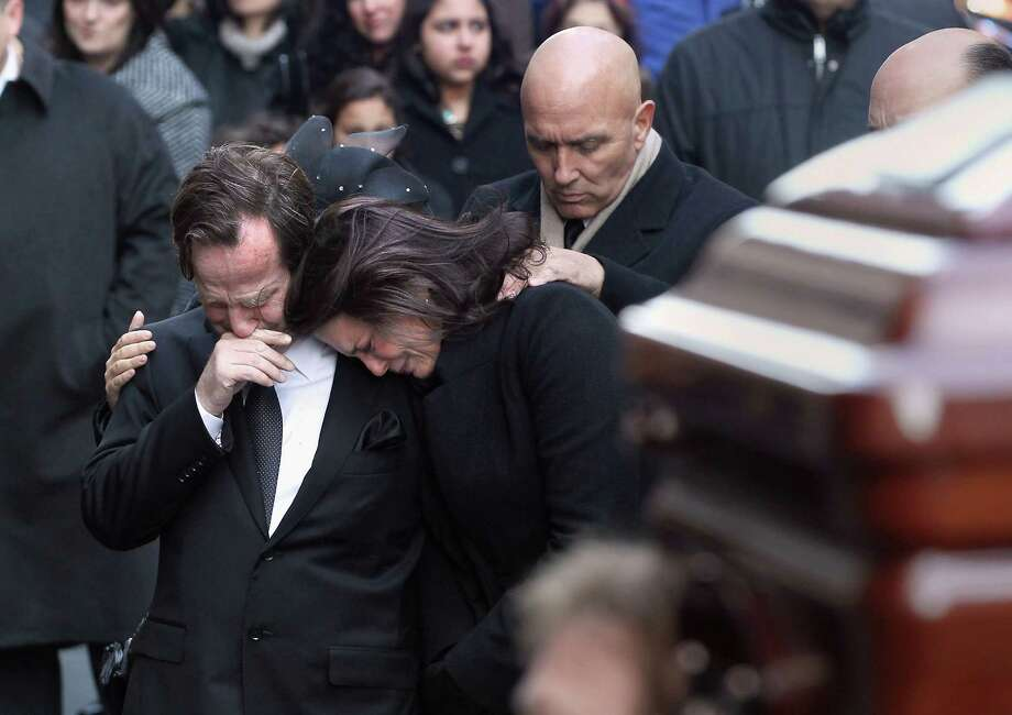 Matthew and Madonna Badger embrace as the casket of one of their three daughters arrives for funeral services on January 5, 2012 in New York City. Hundreds of people attended the service at St. Thomas Church to remember Lilian Badger, 9, and her twin sisters Sarah and Grace, 7, who died in a fire in Stamford, CT on Christmas morning. The girls' mother, Madonna Badger, and her friend Michael Borcina (in photo with hand on Madonna's shoulder) were the only survivors of the fire Photo: John Moore/Getty Images,  John Moore/Getty Images / 2012 Getty Images