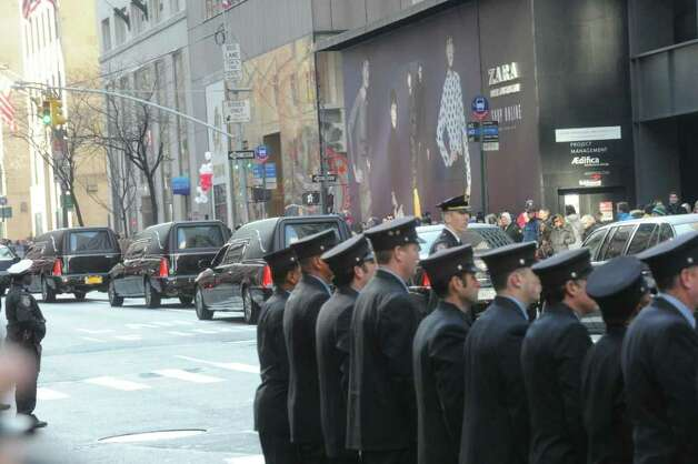 Stamford firefighters in formation as they watch the procession leave after the funeral services for the three Badger sisters, Lilian, Sarah and Grace, at St. Thomas Church Fifth Avenue in Manhattan, N.Y., on Thursday, January 5, 2012. The sisters were killed along with their grandparents, Lomer and Pauline Johnson, when their mother's Shippan home burned down on Christmas Day. Photo: Keelin Daly / Stamford Advocate