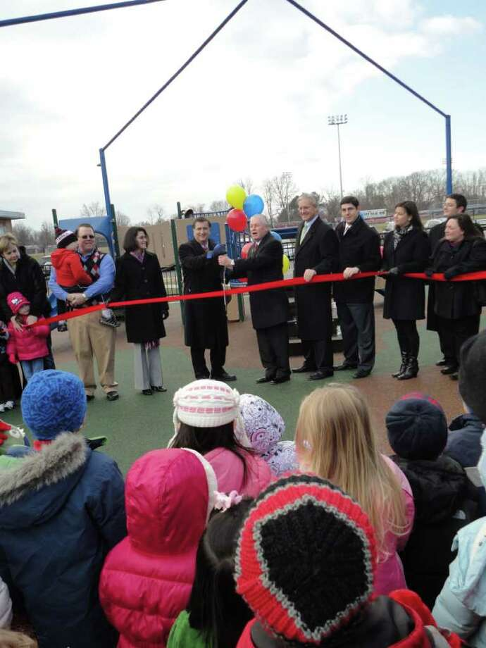 Town and education officials, led by First Selectman Michael Tetreau and Superintendent of Schools David Title, prepare to cut the ribbon on a new all-access playground at the Early Childhood Center Thursday. Photo: Meg Barone / Fairfield Citizen freelance