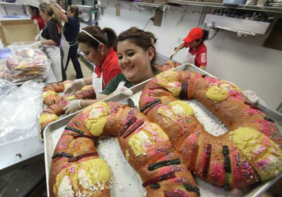"Cinthia Tejeda carries ""Roscas"" or Kings Bread, a doughnut shaped bread with a plastic baby Jesus hidden inside to be shared with family,  to celebrate El Dia de los Reyes Magos or Three Kings Day at El Bolillo Bakery on Thursday, Jan. 5, 2012, in Houston. Photo: Mayra Beltran, Houston Chronicle / © 2011 Houston Chronicle"