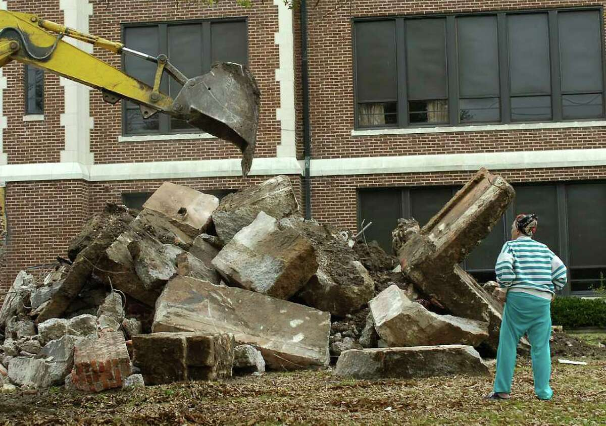 The Ambush Demolition excavator worked the pile of debris in April, 2010 as Deloris Coudrain makes her way to it in her attempt to get a brick for her sister who attended South Park High School. Dave Ryan/The Enterprise