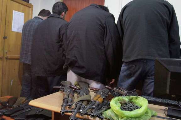 Detained members of Garda World private security company are seen near their confiscated arms during a news event in Kabul, Afghanistan, Thursday, Jan. 5, 2012. Two British nationals along with their Afghan colleagues from Garda World private security company operating in Kabul have been detained for alleged offences involving illegal weapons. (AP Photo/Musadeq Sadeq)
