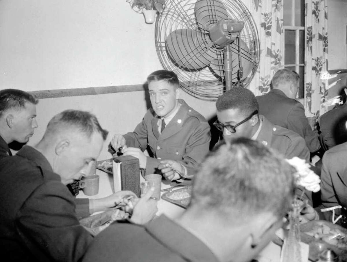Pvt. Elvis Presley puts away a meal of fried fish and french fries after his arrival at Fort Hood on March 28, 1958, to begin eight weeks of basic military training in the 2nd Armored Division.