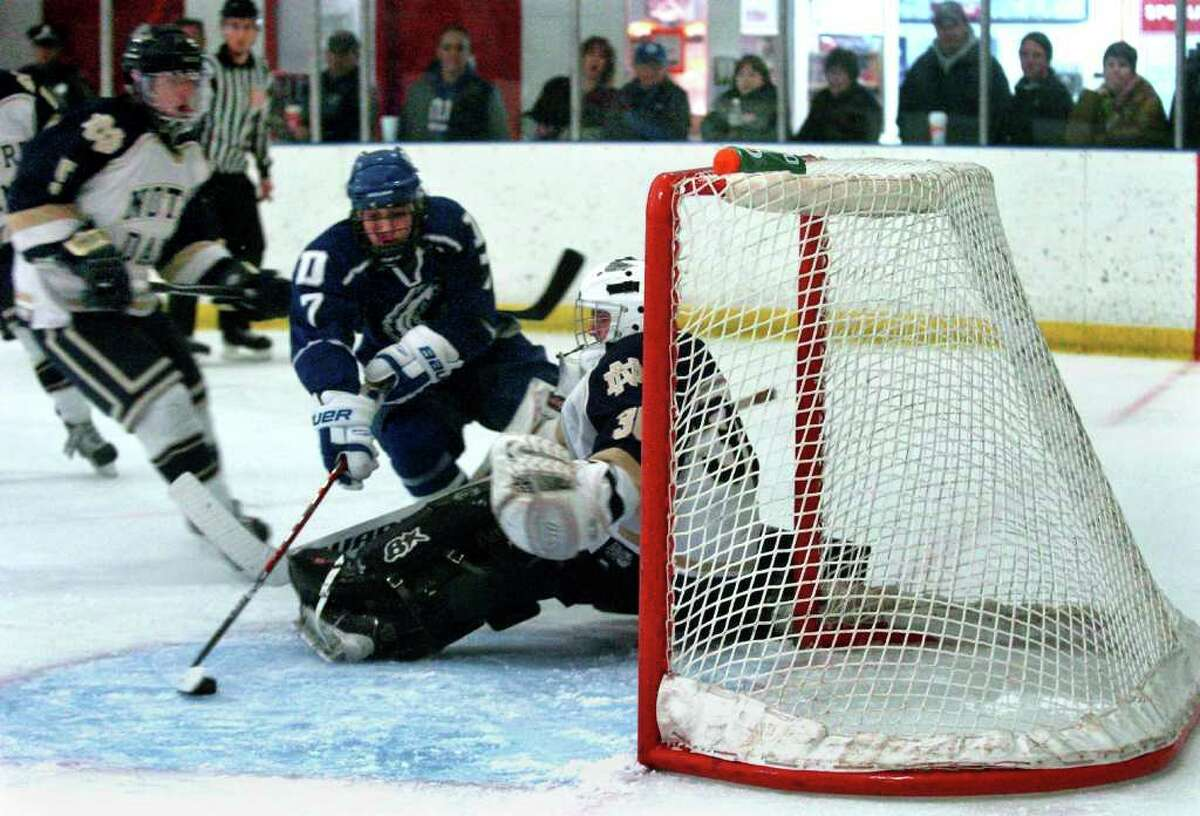 Darien's Jack Knowlton gets this puck past Notre Dame of Fairfield goalie Scott Kline for a point, during boys hockey action in Milford, Conn. on Thursday January 5, 2012.