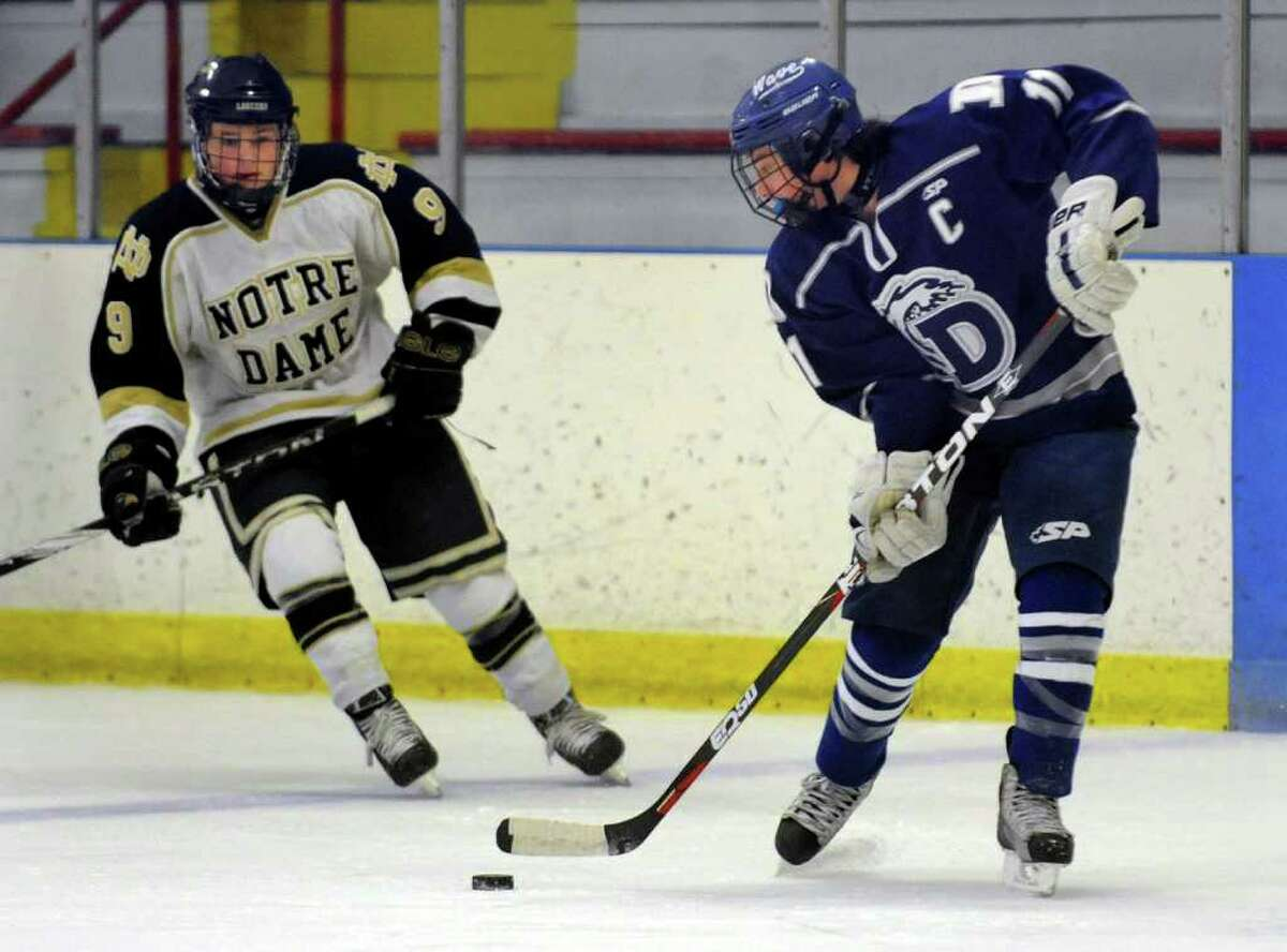 Darien's #11 Hank Glick, right, intercepts the puck as Notre Dame of Fairfield's #9 CJ Litwin converges, during boys hockey action in Milford, Conn. on Thursday January 5, 2012.