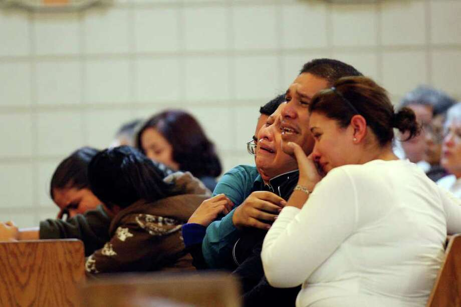 Noralva Gonzalez (center) cries as she and husband Jaime Gonzalez Sr. mourn the death of their son, 15-year-old Jaime Gonzalez Jr., during a memorial Mass at Holy Family Church in Brownsville. The teen was shot and killed by police Wednesday. Photo: JERRY LARA, San Antonio Express-News / SAN ANTONIO EXPRESS-NEWS
