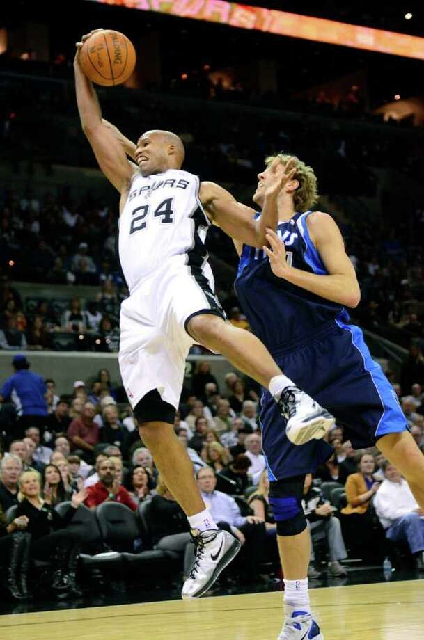 San Antonio Spurs forward Richard Jefferson grabs a rebound in front of Dallas Mavericks forward Dirk Nowitzki, of Germany, during the first half of an NBA basketball game in San Antonio, Thursday, Jan. 5, 2012. Photo: AP