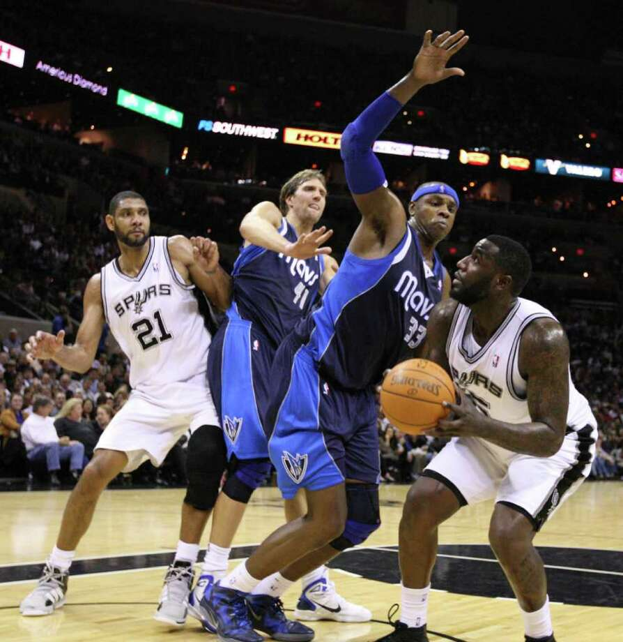 San Antonio Spurs forward DeJuan Blair (45) shoots against Dallas Mavericks center Brendan Haywood (33), Dallas Mavericks forward Dirk Nowitzki (41) and San Antonio Spurs forward Tim Duncan (21) during second half action Thursday Jan. 5, 2012 at the AT&T Center. Photo: EDWARD A. ORNELAS, Express-News / SAN ANTONIO EXPRESS-NEWS (NFS)
