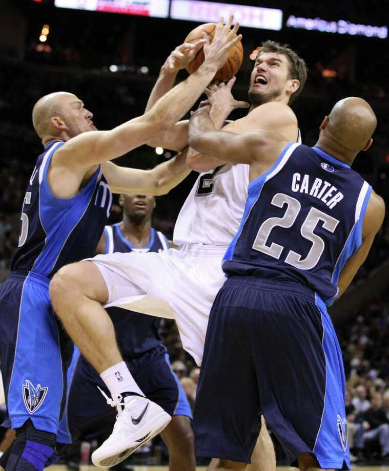 San Antonio Spurs forward Tiago Splitter (22) is fouled by Dallas Mavericks guard Vince Carter (25) near Dallas Mavericks forward Brian Cardinal (35) during second half action Thursday Jan. 5, 2012 at the AT&T Center. Photo: EDWARD A. ORNELAS, Express-News / SAN ANTONIO EXPRESS-NEWS (NFS)
