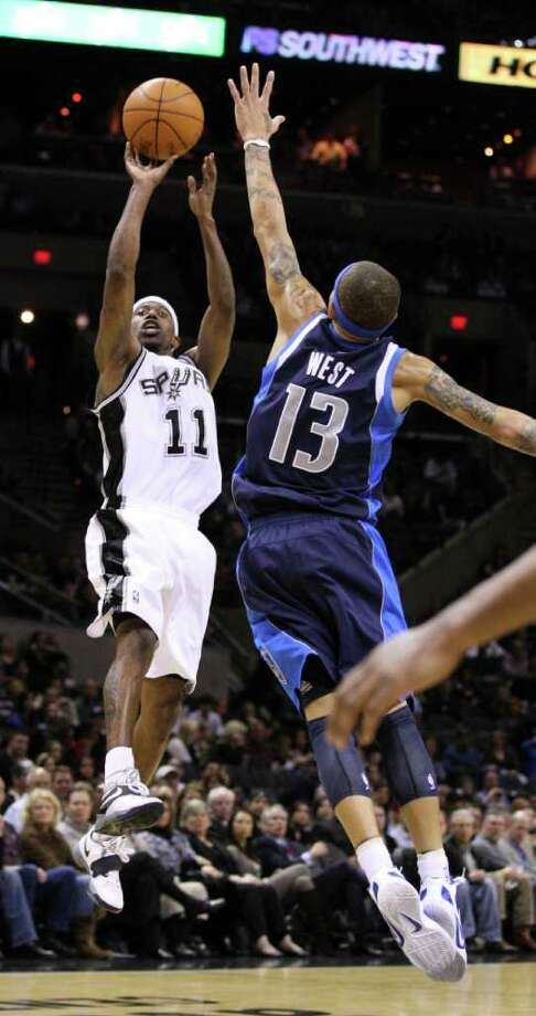 San Antonio Spurs guard T.J. Ford (11) shoots over Dallas Mavericks guard Delonte West (13) during second half action Thursday Jan. 5, 2012 at the AT&T Center.  The Spurs won 93-71. Photo: EDWARD A. ORNELAS, Express-News / SAN ANTONIO EXPRESS-NEWS (NFS)