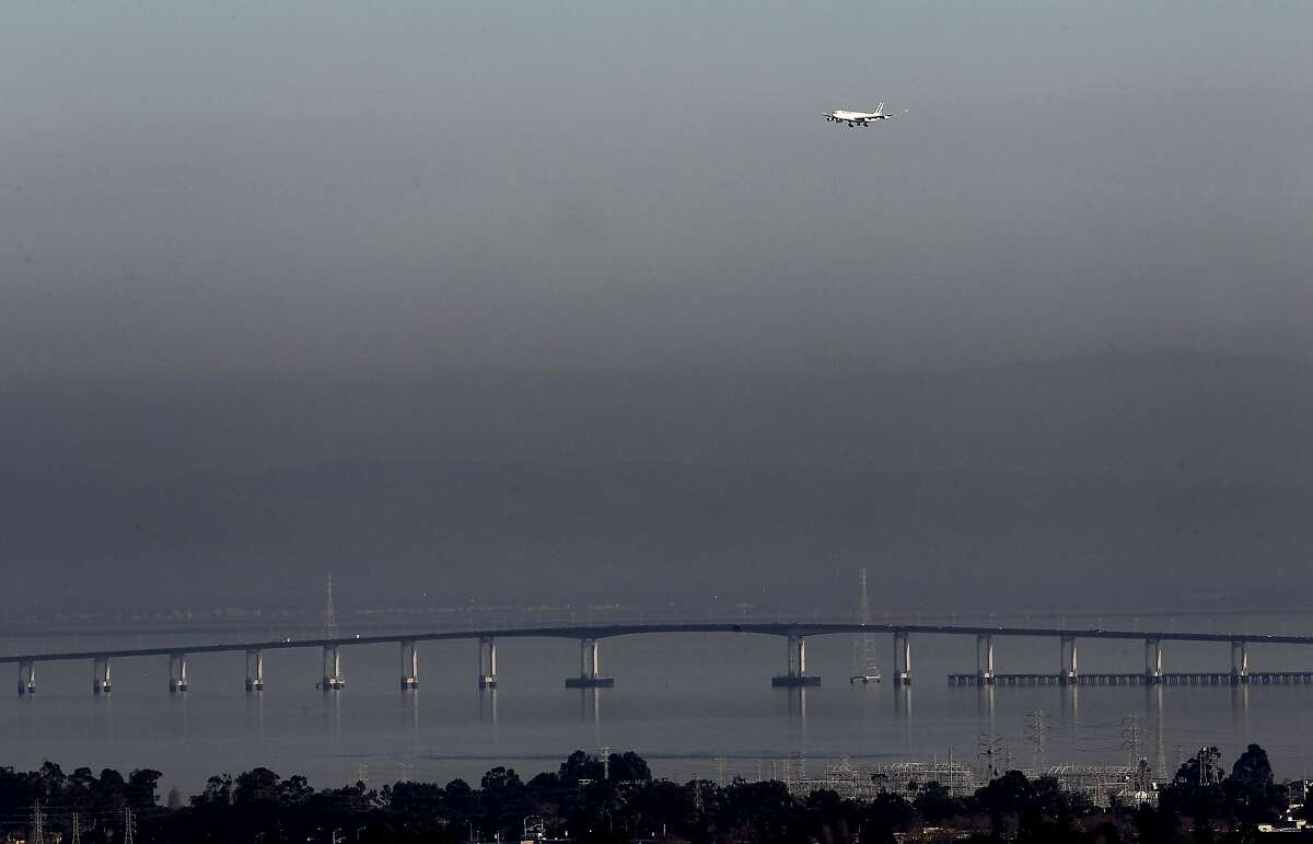 A plane approaches SFO from the south over the San Mateo Bridge and a layer of smog Wednesday January 4, 2011. Spare the Air days are becoming commonplace in the Bay Area with so little rain or wind in the forecast, making it difficult to have a wood fire this winter.