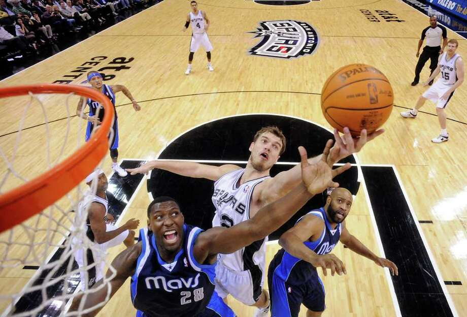 San Antonio Spurs' Tiago Splitter grabs for a rebound between Dallas Mavericks' Ian Mahinmi and Dallas Mavericks' Vince Carter during second half action Thursday Jan. 5, 2012 at the AT&T Center. The Spurs won 93-71. Photo: EDWARD A. ORNELAS, Express-News / SAN ANTONIO EXPRESS-NEWS (NFS)