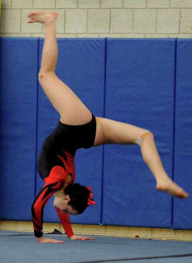New Canaan's Ellen Hoover does her floor routine during a gymnastics meet at Weston Middle School Thursday Jan. 5, 2012. Photo: Autumn Driscoll / Connecticut Post