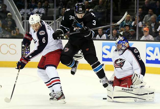 Columbus Blue Jackets goalie Curtis Sanford (30) deflects a shot next to San Jose Sharks center Logan Couture (39) and defenseman Nikita Nikitin (6), of Russia, during the first period of an NHL hockey game in San Jose, Calif., Thursday, Jan. 5, 2012. (AP Photo/Marcio Jose Sanchez) Photo: Marcio Jose Sanchez, Associated Press