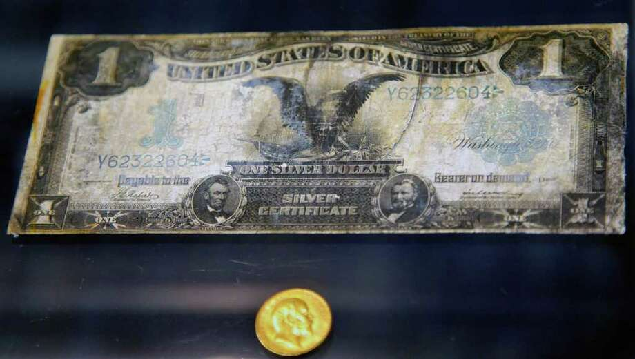 A bank note dollar bill and gold coin from the Titanic wreckage are among a sampling of Titanic artifacts previewed on Thursday, Jan. 5, 2012 in New York.  The complete collection of artifacts recovered from the wreck site of the RMS Titanic will be auctioned by Guernsey's Auction House in April. Photo: Bebeto Matthews, AP / AP