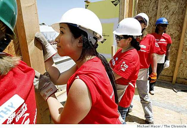 Volunteers, Victoria Chua, (left center) and her mother Virgie, (on her right)  join a group of women, mostly mothers and daughters, are helping to put construct a building in, Oakland, Calif. on Saturday May 9, 2009, for Habitat for Humanity. Photo: Michael Macor, The Chronicle