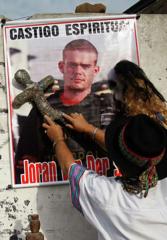 A shaman performs a ritual for the spiritual punishment of Joran van der Sloot, whose picture is posted on the wall, before Van der Sloot's trial outside San Pedro prison in the Lurigancho area of Lima, Peru, Friday Jan. 6, 2012.  Van der Sloot, 24, goes on trial Friday for the 2010 murder of the 21-year-old Stephany Flores, of Peru, nearly seven years after he became the prime suspect in the unsolved disappearance of an American teenager on holiday in Aruba. (AP Photo/Karel Navarro) Photo: Karel Navarro, Associated Press / AP