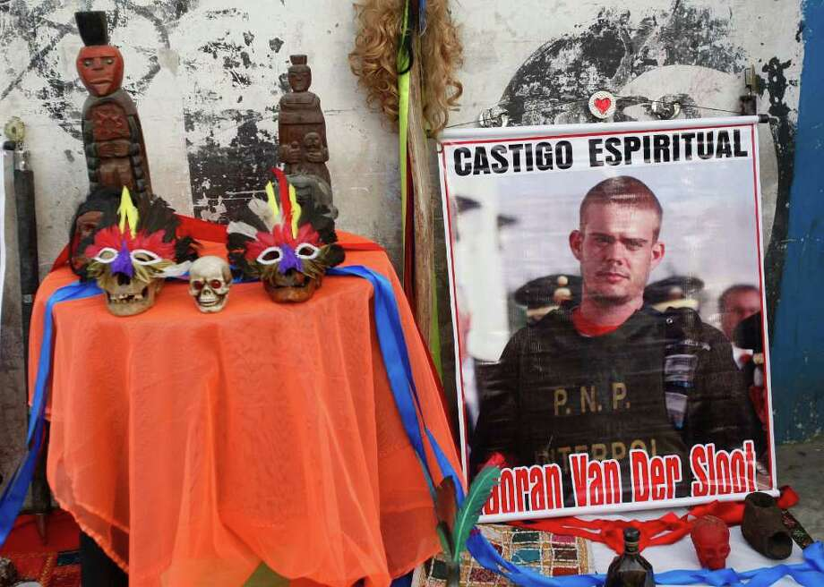 "A poster of Joran Van der Sloot that reads in Spanish ""Spiritual punishment"" sits among items from a shaman ritual outside San Pedro prison where his trial will be start in the Lurigancho area of Lima, Peru, Friday Jan. 6, 2012.  Van der Sloot goes on trial Friday for the murder of a young Peruvian woman, nearly seven years after he became the prime suspect in the unsolved disappearance of an American teenager on holiday in Aruba.  Van der Sloot, 24, is charged with killing 21-year-old Stephany Flores in his Lima hotel room on May 30, 2010. (AP Photo/Karel Navarro) Photo: Karel Navarro, Associated Press / AP"