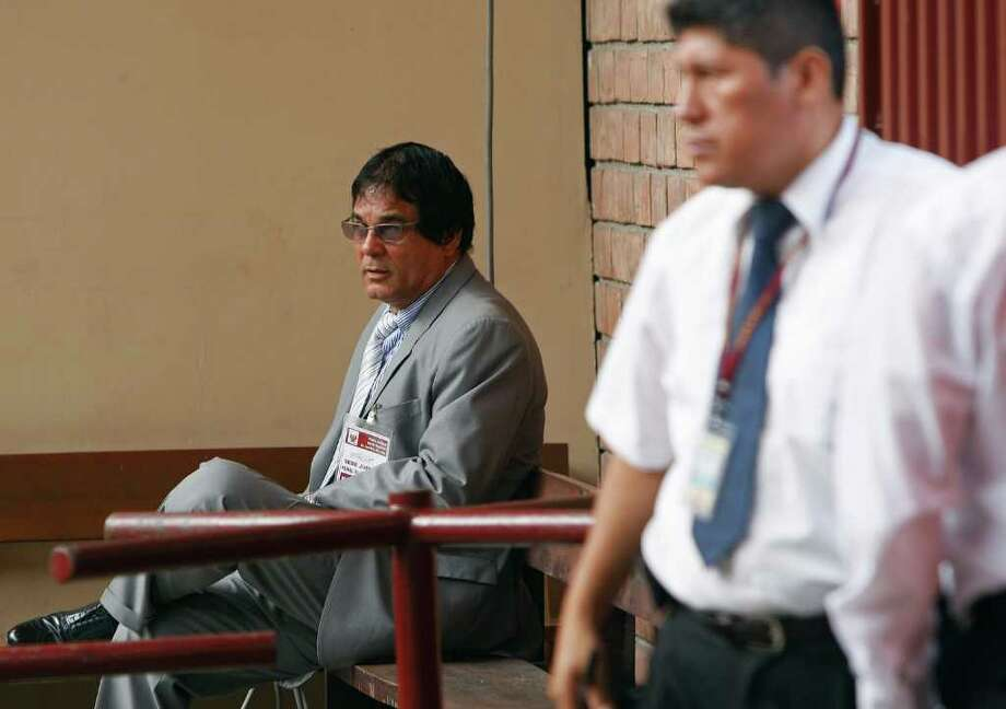 Ricardo Flores, left, father of slain Stephany Flores, waits as jail workers pass by before the start of Joran Van der Sloot's trial inside San Jorge prison in the Lurigancho area of Lima, Peru, Friday Jan. 6, 2012.  Van der Sloot, 24, stands trial Friday for the 2010 murder of the 21-year-old Flores, of Peru, nearly seven years after he became the prime suspect in the unsolved disappearance of an American teenager on holiday in Aruba. (AP Photo/Karel Navarro) Photo: Karel Navarro, Associated Press / AP
